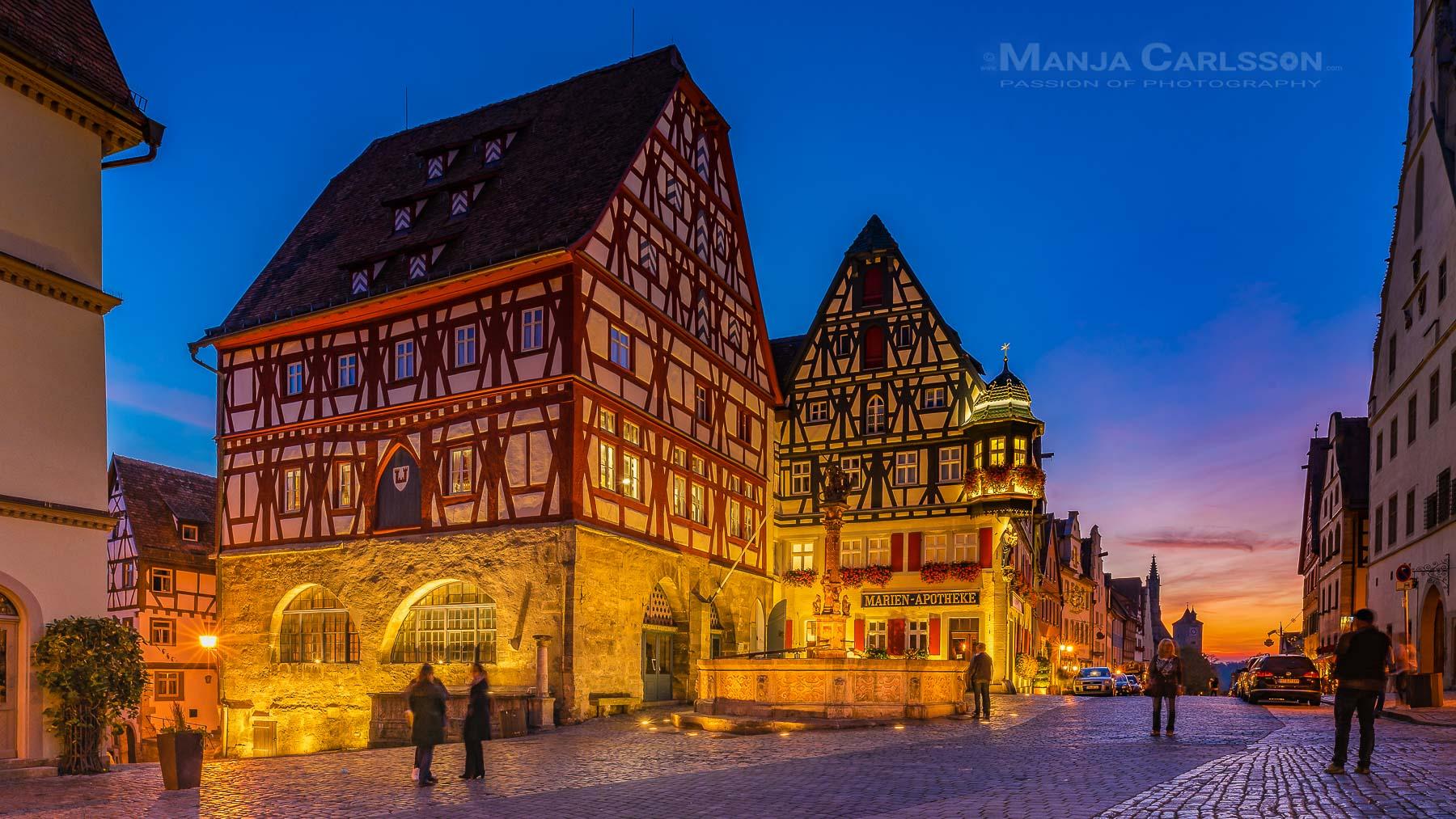 Rothenburg ob der Tauber der weltbekannte St. Georgs Brunnen am Marktplatz zur blauen Stunde mit knallorangefarbenen Sonnenuntergang im Hintergrund